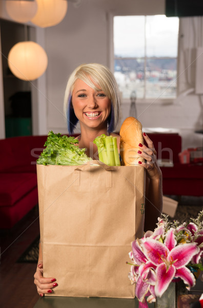 Attractive Female Homemaker Sets Grocery Bag on Counter Stock photo © cboswell