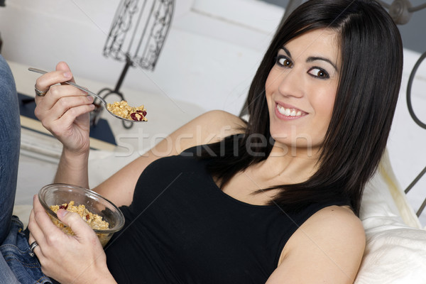 Stock photo: Smiling Young Adult Woman Eats Cereal With Fruit