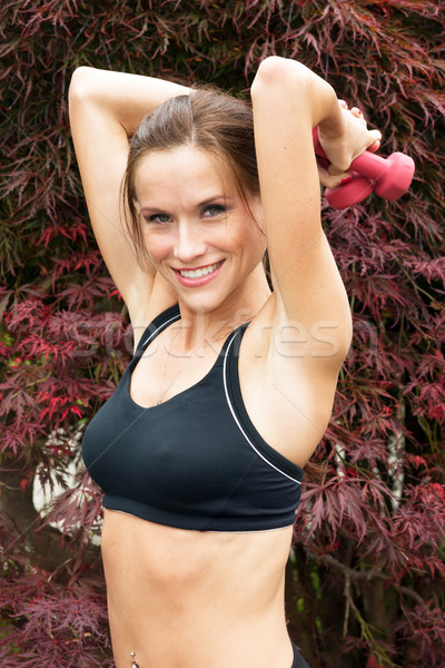 Attractive Woman lifts barbells overhead during outdoor workout  Stock photo © cboswell