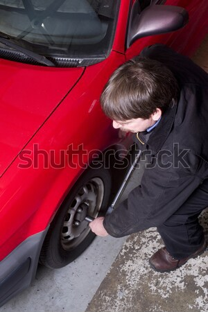 Automotive Technician Auto Mechanic Loosens Lug Nut Front Tire Stock photo © cboswell