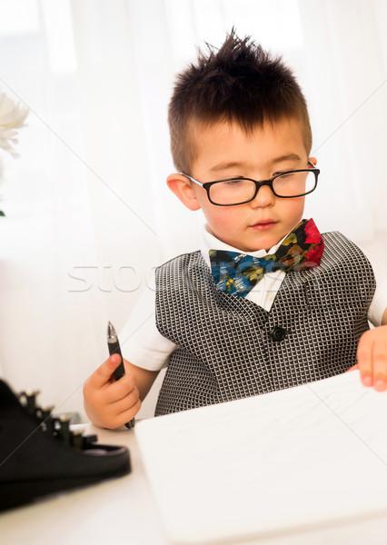 Intellettuale uomo d'affari firma giornali desk Foto d'archivio © cboswell