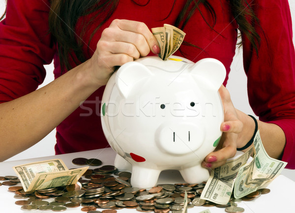 Woman Stuffing US Currency Coins Piggy Bank Cash Savings Stock photo © cboswell