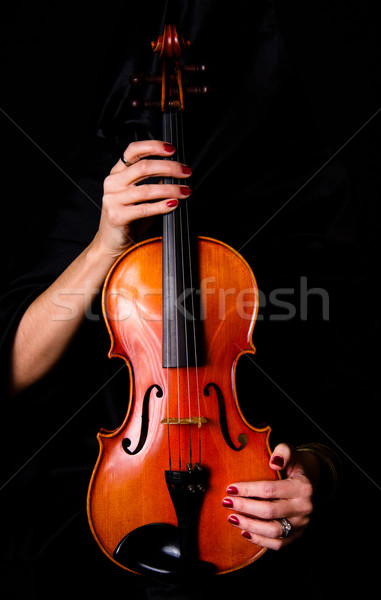 Female Violinist Holds Bow Across Saturated Musical Violin Acoustic  Stock photo © cboswell