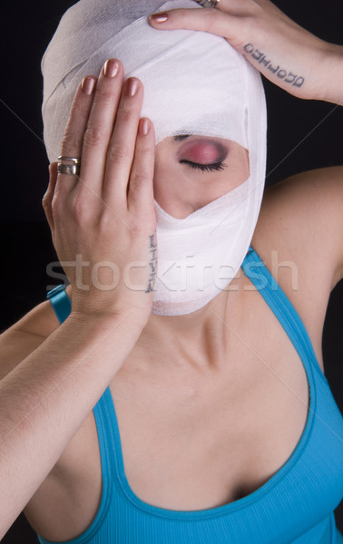 Female Holds Face First Aid Gauze Wrapped Head Injury Pain Stock photo © cboswell