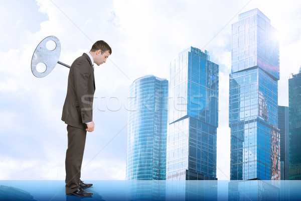 Businessman with key in back and city scape Stock photo © cherezoff