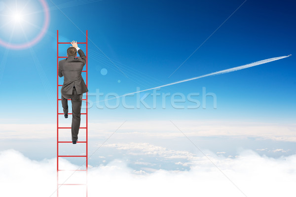 Businessman climbing ladder in sky Stock photo © cherezoff