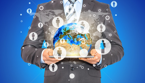 Businessman hold tablet pc, Earth and contacts Stock photo © cherezoff