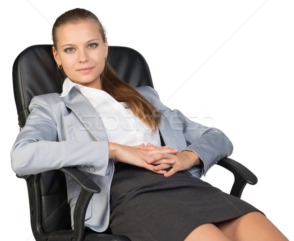 Businesswoman back in office chair, with hands clasped over her stomach Stock photo © cherezoff