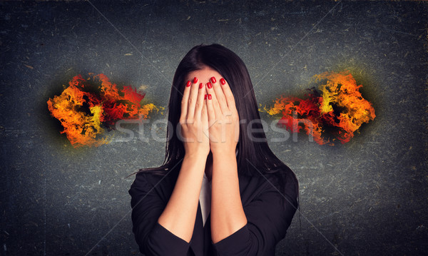 Crying woman with fire from ears. Concrete gray wall as backdrop Stock photo © cherezoff