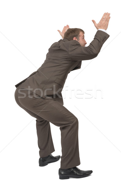 Businessman under heavy empty space, side view Stock photo © cherezoff