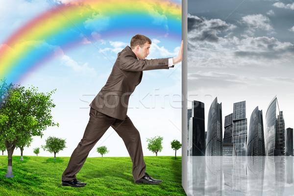 Businessman changing city on nature landscape Stock photo © cherezoff