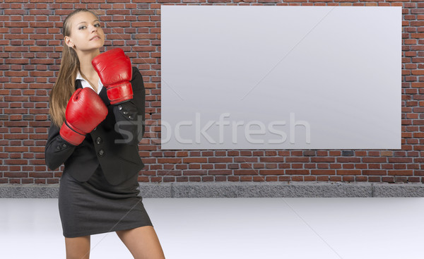Businesswoman posing in boxing gloves. Brick wall with blank banner as backdrop Stock photo © cherezoff