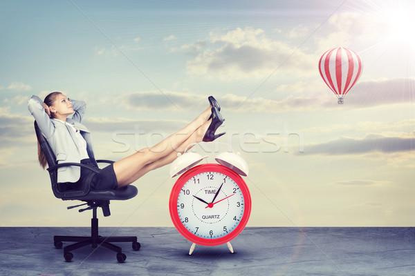 Businesswoman sitting with her feet up on alarm-clock  Stock photo © cherezoff