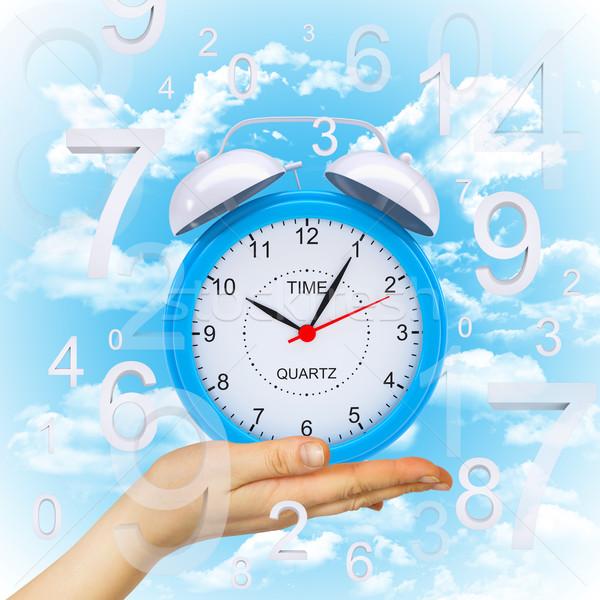 Hand hold alarm clock with figures Stock photo © cherezoff