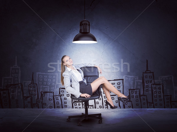 Centered woman wearing jacket, blouse sitting with legs crossed. Background sketch of buildings Stock photo © cherezoff