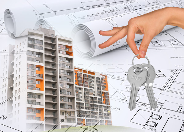 Buildings with hand holding keys and drafts Stock photo © cherezoff