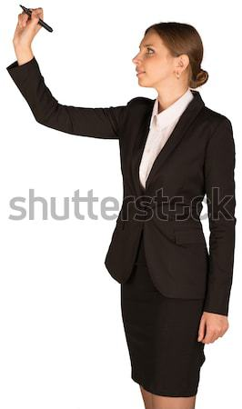 Beautiful girl in business suit holding pen and writing Stock photo © cherezoff