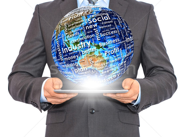 Businessman holds tablet pc with Earth in hand Stock photo © cherezoff