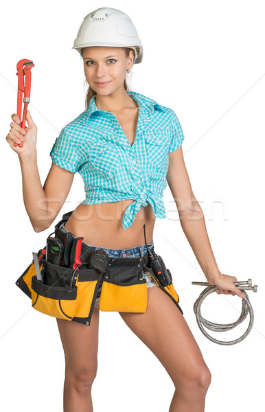 Pretty girl in helmet, shorts, shirt, tool belt with tools holding flexible hose and wrench Stock photo © cherezoff