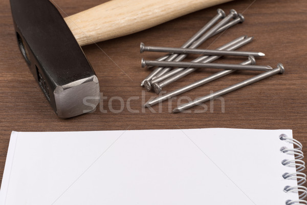Hammer with note pad and nails on table Stock photo © cherezoff