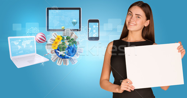 Beautiful businesswoman holding paper holder. Electronics, Earth with buildings and trees Stock photo © cherezoff