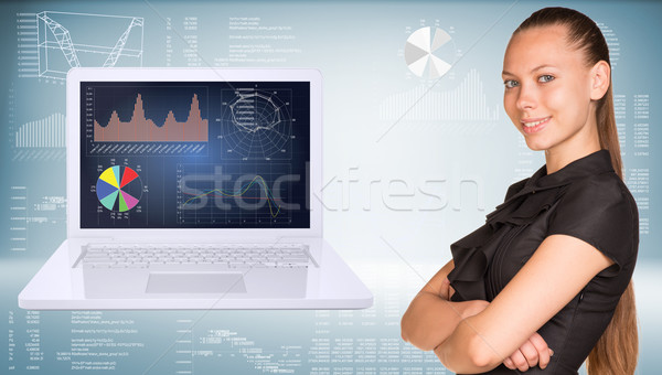 Beautiful businesswoman in dress smiling and looking at camera. Open laptop with graphs on screen ar Stock photo © cherezoff
