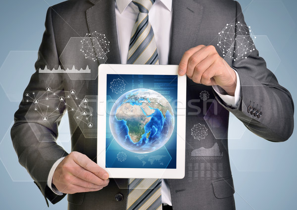 Man hands using tablet pc. Image of Earth and network on screen Stock photo © cherezoff