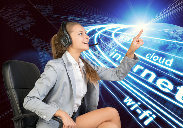Businesswoman in headset touching or pressing something Stock photo © cherezoff
