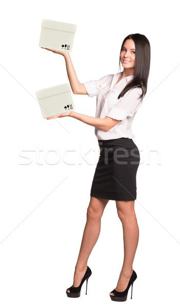 Smiling businesslady holding two white boxes Stock photo © cherezoff