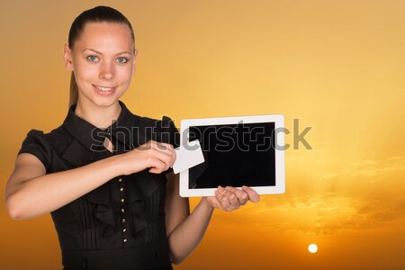 Beautiful businesswoman holding tablet PC and business card in front of screen. Bright sky at sunset Stock photo © cherezoff