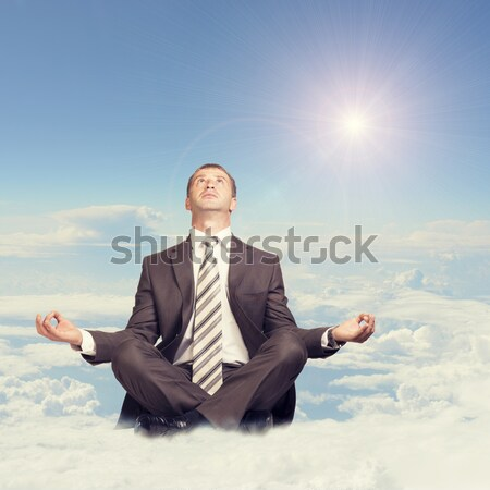 Businessman sitting in lotus position on cloud, looking up Stock photo © cherezoff