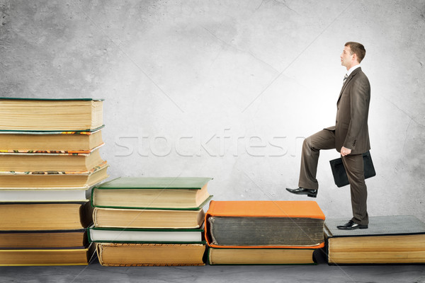 Businessman with portfolio goes up stairs of books Stock photo © cherezoff