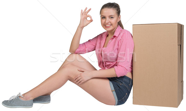Woman sitting next to cardboard box, showing ok sign Stock photo © cherezoff
