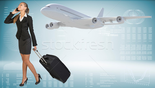 Businesswoman carrying suitcase while talking on the phone. Image of flying airliner beside Stock photo © cherezoff