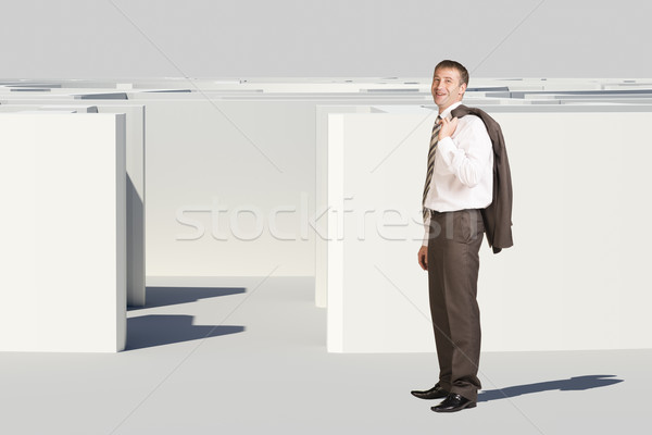Businessman with suit on shoulder goes in maze Stock photo © cherezoff