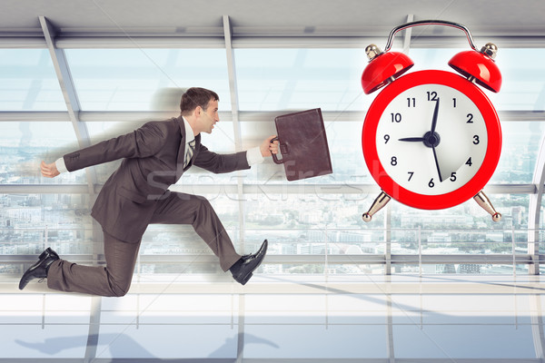 Businessman running with alarm clock background Stock photo © cherezoff