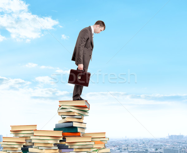 Businessman looking down from piles of books Stock photo © cherezoff