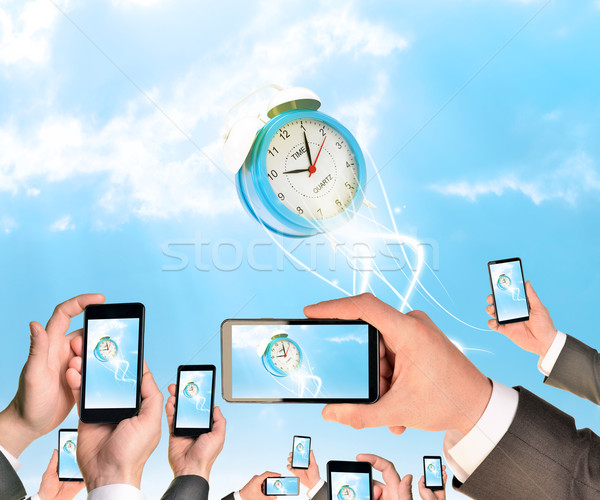 Hands holding smart phones and shoot video as falling alarm clock Stock photo © cherezoff