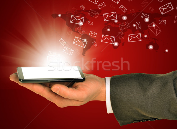 Business man holding a mobile phone within left hand Stock photo © cherezoff
