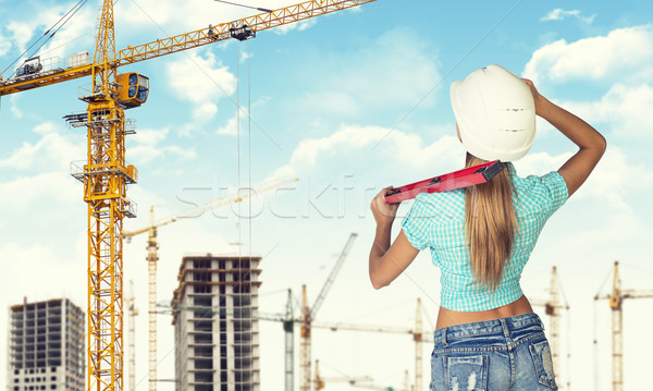 Woman in helmet stands backwards, holding building level. Looks at crane. Construction site as backd Stock photo © cherezoff