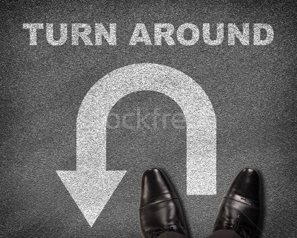 Shoes standing on asphalt road with U-turn sign and text turn around Stock photo © cherezoff