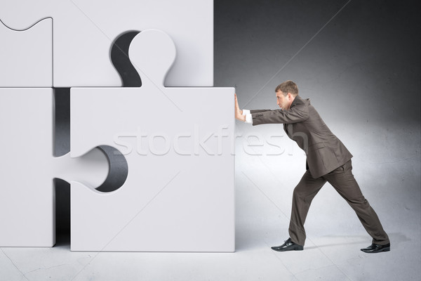 Man in suit pushing grey puzzle piece Stock photo © cherezoff