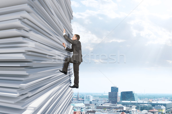 Businessman climbing up a huge stack of paper Stock photo © cherezoff