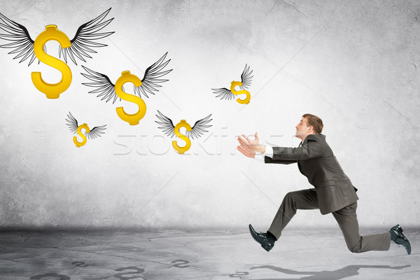 Business man running to catch flying dollar sign Stock photo © cherezoff