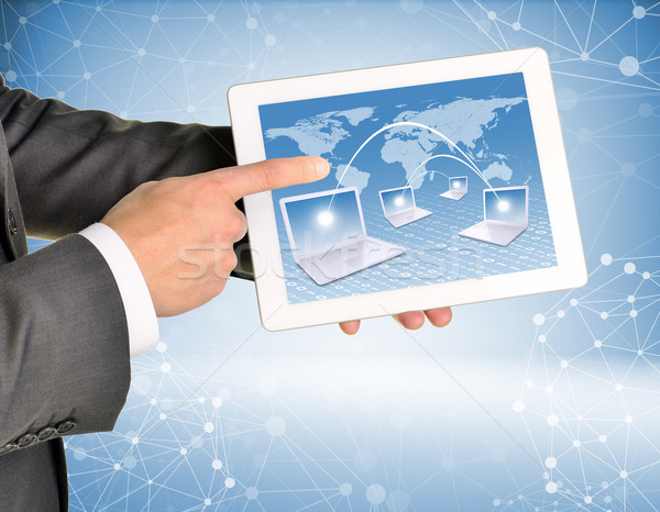 Man hands using tablet pc. Image of world map and laptops on screen Stock photo © cherezoff