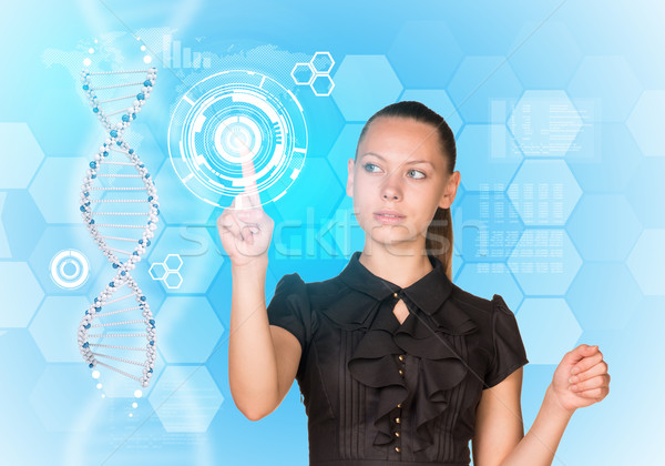 Beautiful businesswoman in dress presses finger on model of DNA Stock photo © cherezoff