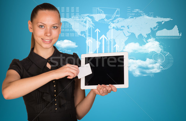 Beautiful businesswoman holding tablet PC. World map and hi-tech graphs with various data as backdro Stock photo © cherezoff