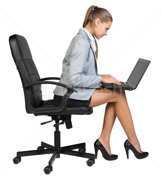 Businesswoman on office chair operating laptop  Stock photo © cherezoff