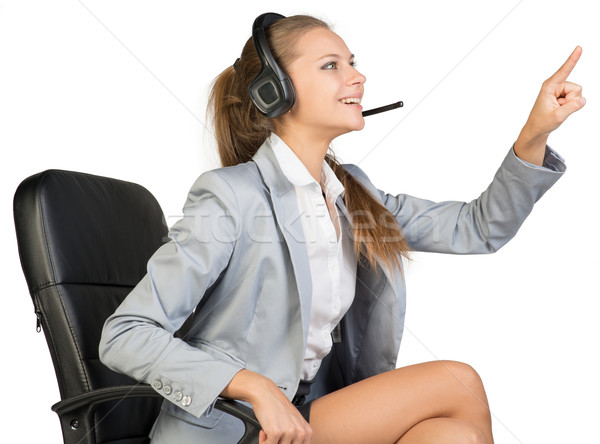 Businesswoman in headset sitting on office chair touching or pressing something Stock photo © cherezoff