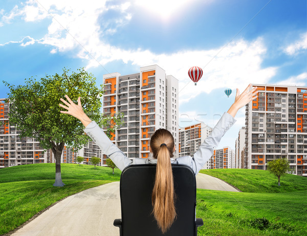 Businesswoman sitting on office chair. Green hills with buildings and sky Stock photo © cherezoff